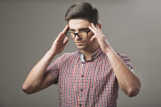 メガネをかけて思慮深いハンサムな若い男