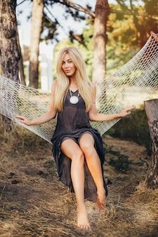 黒いプレーンサンドレスの若い魅力的なブロンドの女の子は、森や公園のハンモックに座っています。美しい素足。キャンプ、コンセプト