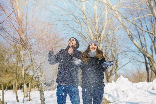 晴れた日に雪を投げることによって冬の公園で楽しんでいるカップル。