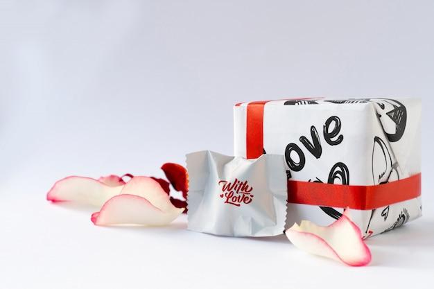 Лепестки роз, шоколад и подарок.
