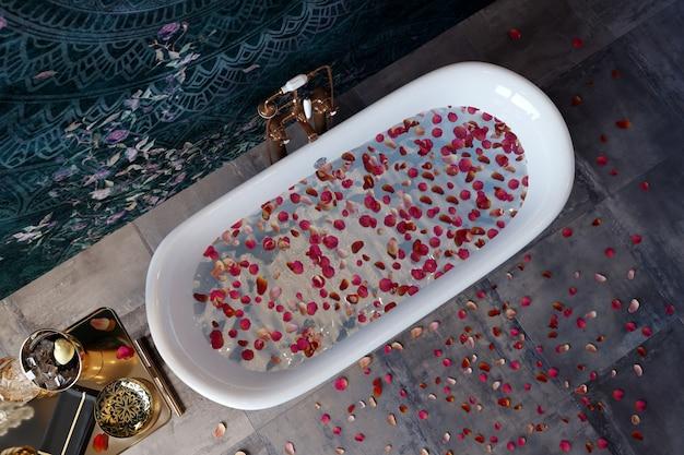 Роскошная ванна стоит в дорогой ванной комнате с лепестками роз.