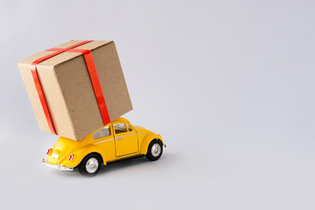 黄色のおもちゃの車は小包を運んでいます。