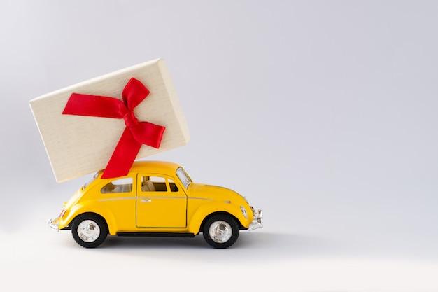 黄色のおもちゃの車は贈り物を運んでいます。