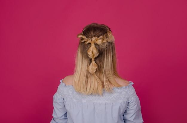 Вид сзади женщины с косой прическа на розовом