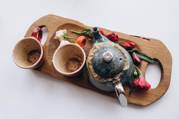 Вид сверху чайник с чашкой с цветами