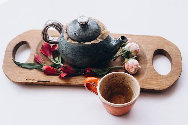 Голубой чайник-заварник керамический и зеленый чай кубок на деревянный стол с цветами. вид сверху.