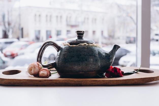 Чашки и чайник на деревенском столе с цветами