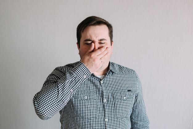 Больной человек чихает