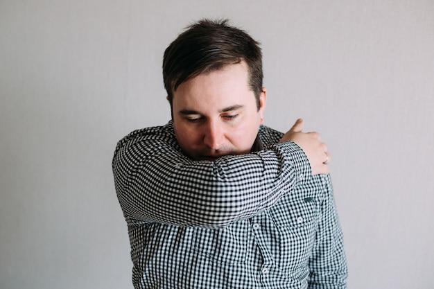 Человек кашляет в локте, чтобы предотвратить распространение коронавируса