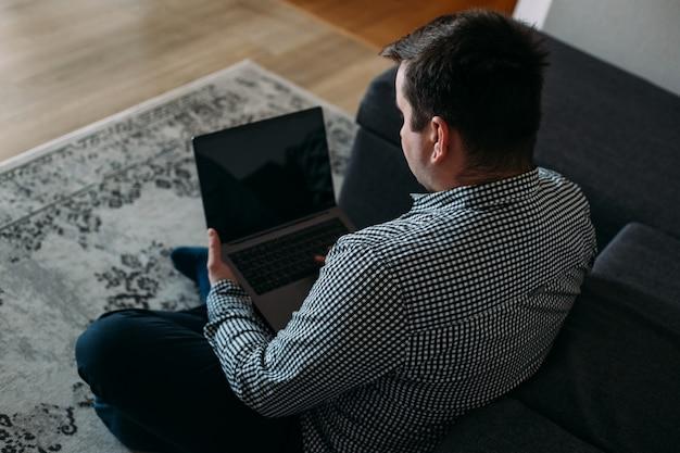 Работая дома, человек, работающий из дома, используя ноутбук
