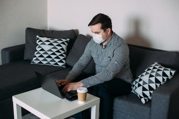 Человек работает на ноутбуке носить маску из домашнего офиса