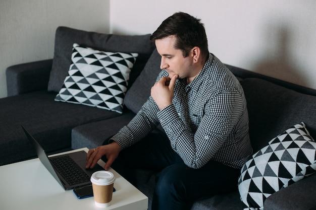 Вдумчивый человек, работающий на компьютере у себя дома