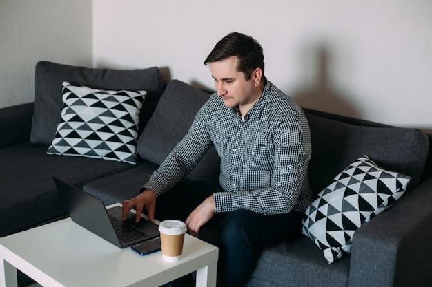 Молодой человек работает на своем компьютере из дома