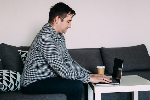 Работая дома, мужчина печатает на компьютере