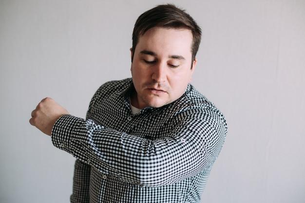 Человек кашляет до локтя, чтобы предотвратить распространение микробов