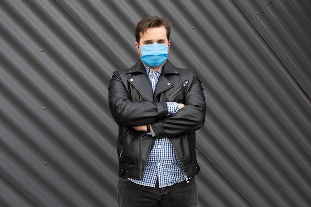 路上でマスクのビジネスマン。建物の外に立っている人