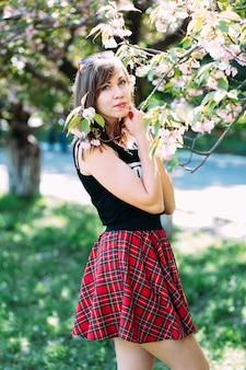 Внешний портрет молодой красивой модной дамы представляя около цветя дерева. цветущий сад с вишневым деревом. копирайс, место для текста