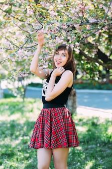 Женщина, делая смешное лицо возле цветущей весной дерево. женщина возле сакуры, цветущая вишня