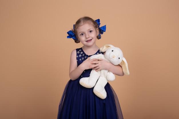 Милая маленькая девочка с игрушечным кроликом, улыбающаяся девочка, изолированная на бежевой нейтральной стене