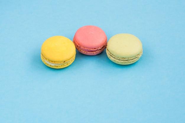 マカロン、青の背景にピンク、黄色、緑のマカロン