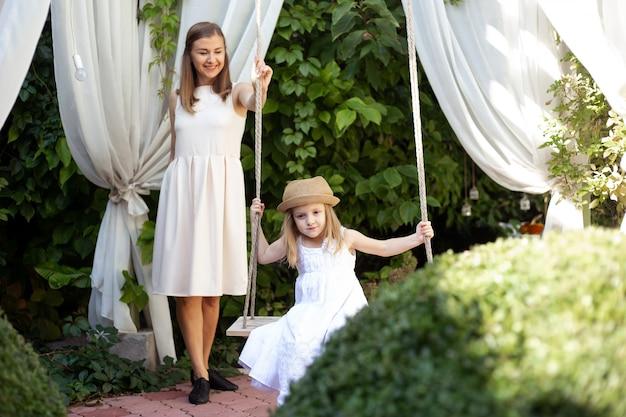 Маленькая девочка и мать веселятся на качелях на открытом воздухе