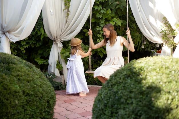 Милая маленькая девочка и мать в прекрасном саду