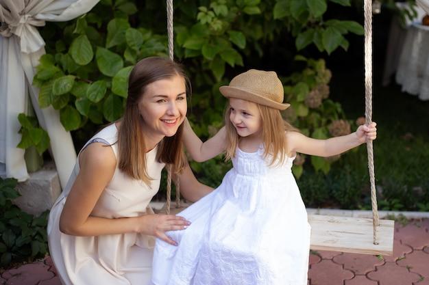 Маленькая девочка в саду и мать