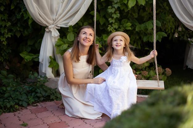 Маленькая девочка и ее мать наслаждаются солнечным летним днем