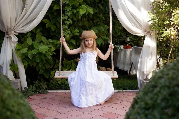 Девушка с удовольствием на качелях в красивом летнем саду в теплый и солнечный день на открытом воздухе