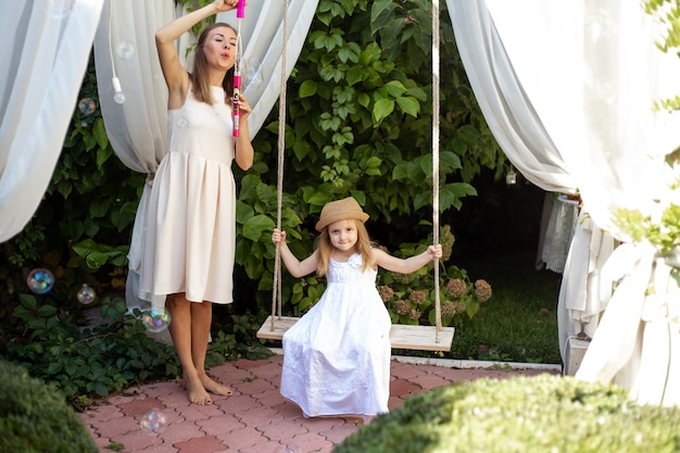 Девочка и мать с удовольствием играют на улице в летний день