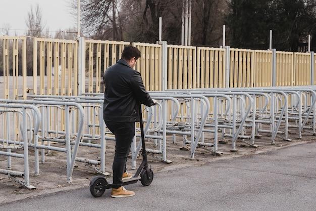 フェンスの背景に折衷的なスクーターに乗る男