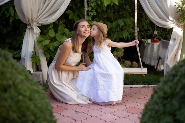 Маленькая девочка целует маму в солнечный летний день