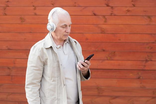 スマートカジュアルスタイルに身を包んだハンサムな老人がスマートフォンを使用していて、ヘッドフォンを着用