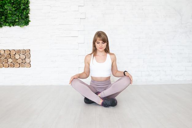 ヨガをやっている床に座っている若い女性