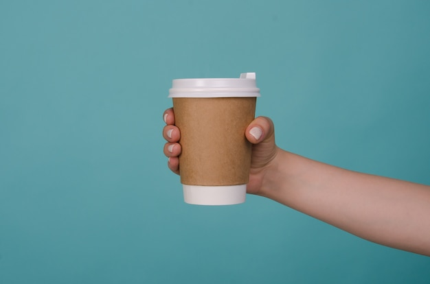 青に分離された女性の手で紙のコーヒーカップ