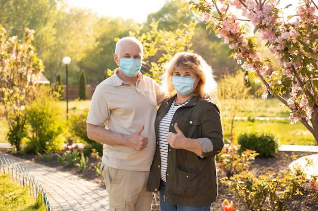 親指を現して、春または夏の自然の外のコロナウイルスから保護するために医療マスクを身に着けている美しい年配のカップル