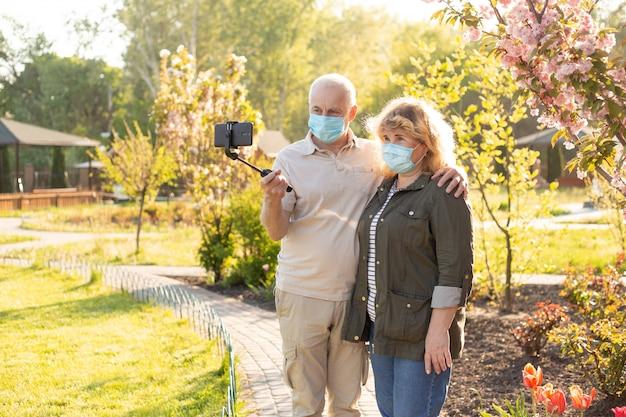 春または夏の公園でコロナウイルスから保護するための医療用マスクを身に着けている自分撮りを作る成熟したカップル