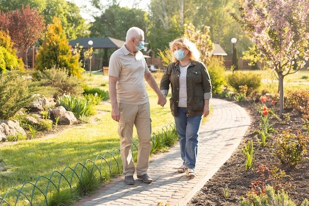 春または夏の日にコロナウイルスから保護するために医療用マスクを着用して公園で年配のカップル