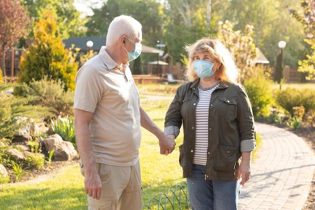 夏の公園でコロナウイルスから保護するために医療マスクを着て幸せな高齢者高齢者のカップル