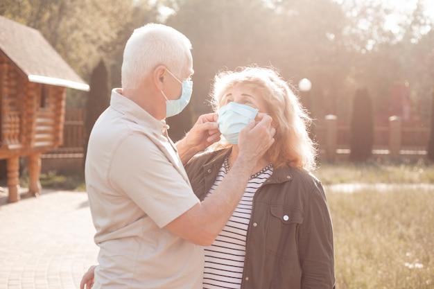 コロナウイルスから保護するために医療マスクを着て恋に幸せな先輩カップル。屋外の公園、コロナウイルス検疫
