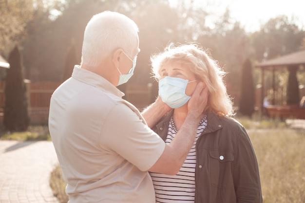 春または夏の自然の中でコロナウイルスの隔離、コロナウイルス隔離から外にコロナウイルスから保護するために医療マスクを着て恋に美しい年配のカップル