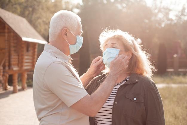 コロナウイルスから保護するために医療用マスクを身に着けている春または夏の公園を受け入れる高齢者のカップル