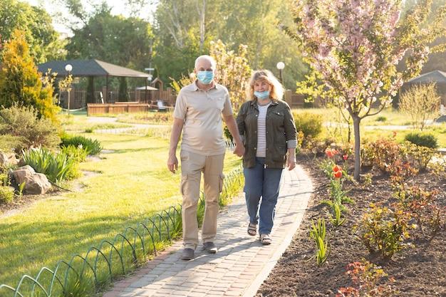 コロナウイルスから保護するために医療マスクを着て恋に幸せな先輩カップル。屋外の公園。