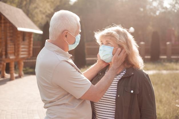 春や夏の自然の外でコロナウイルスから保護するために医療マスクを着て恋に美しい年配のカップル