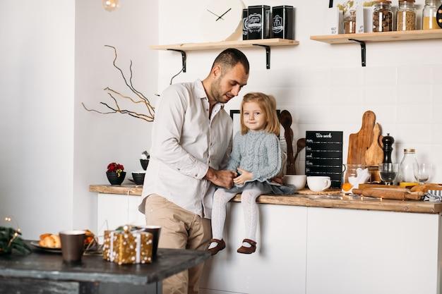 Отец и дочь в кухне дома.