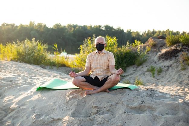 Старший мужчина носить защитную маску, сидя в природе, делая упражнения йоги.