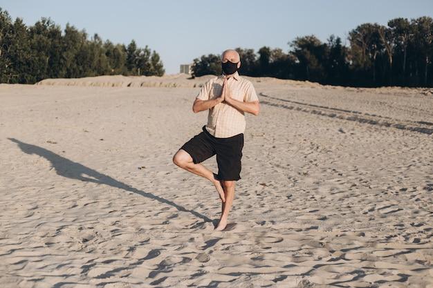 Зрелый человек делает упражнения йоги человек в защитной маске
