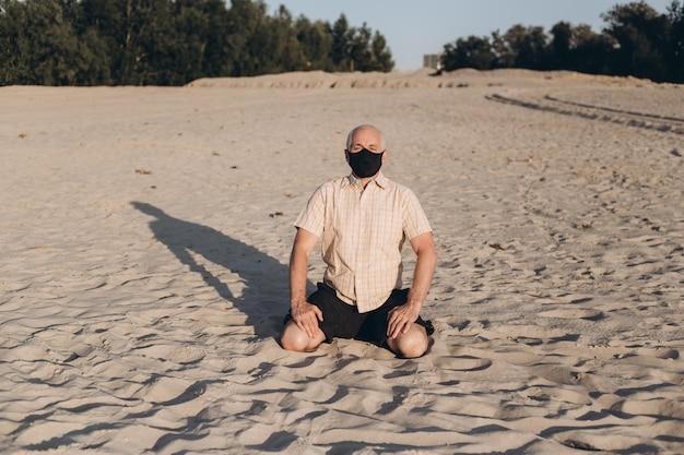 Старший мужчина сидит в природе, ношение медицины защитная маска