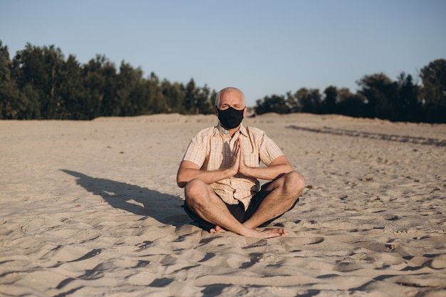 Маска медицины старшего человека нося защитная в представлении лотоса сидя на песок. понятие спокойствия и медитации.