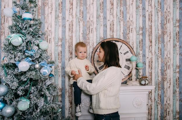 母とクリスマスツリーの近くの小さな男の子。クリスマス、新年、冬、休日の季節の概念。家族。
